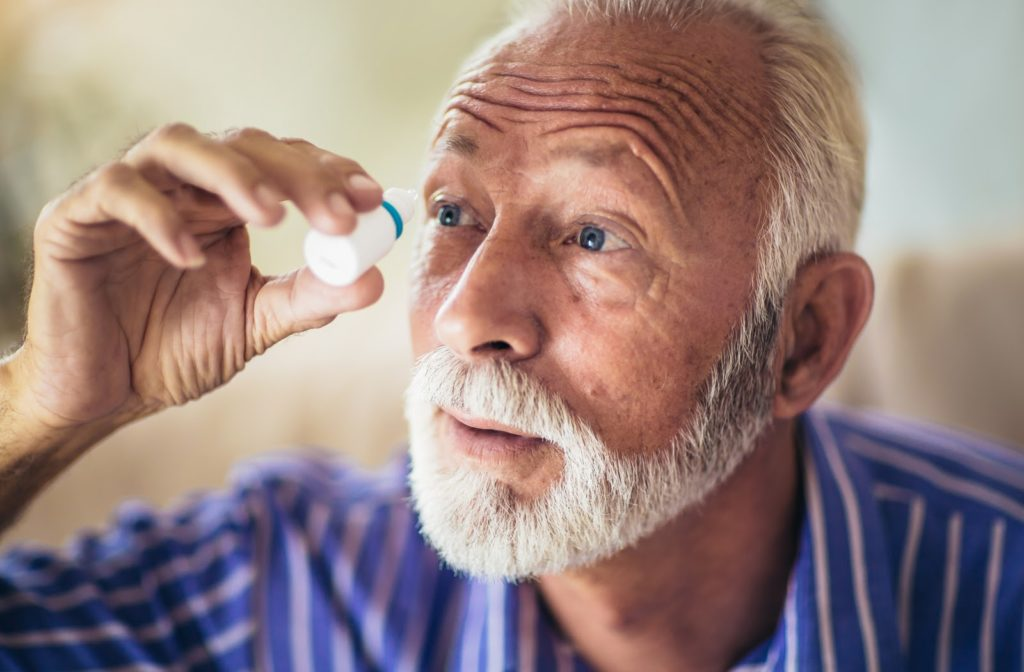 Senior male applying eyedrops to right eye