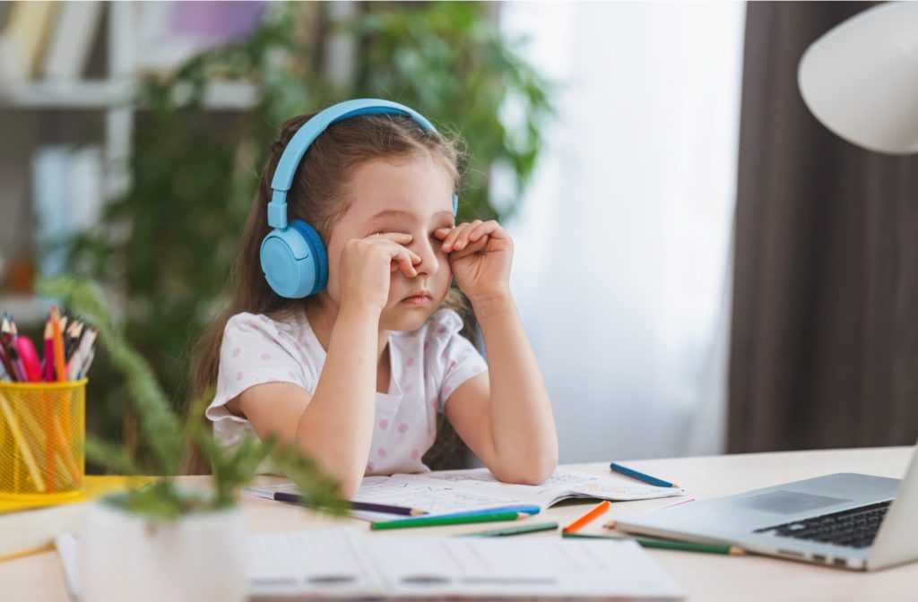 Girl at a computer rubbing her eyes due to digital eye strain.